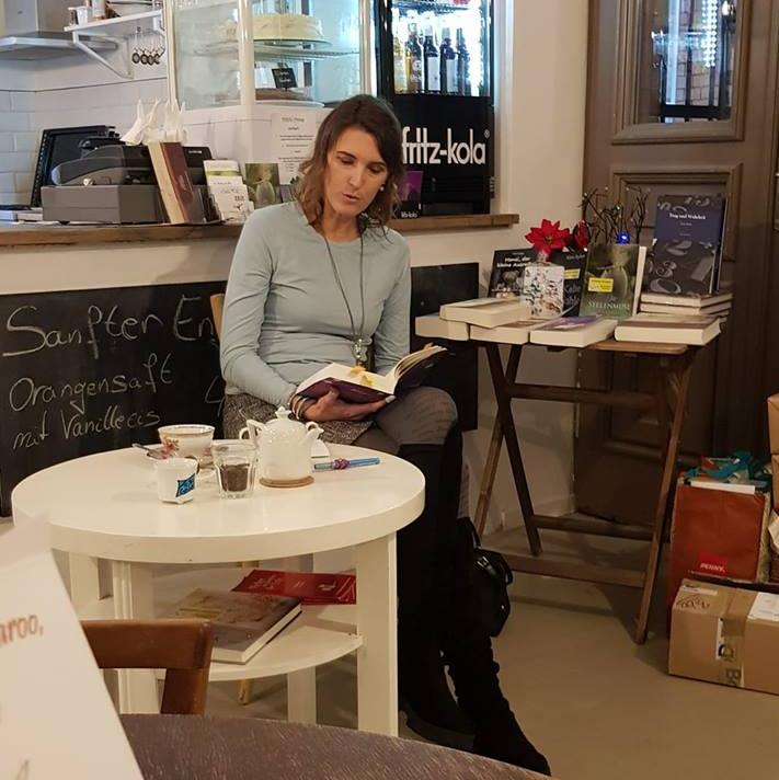 Hier sieht man Alizée Korte lesend im Café Diem in Halle (Saale)